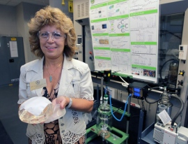 University of Akron Dr. Judit Puskas with a piece of spun Polymer held in front of a traditional silicone implant. (Phil Masturzo/Akron Beacon Journal)